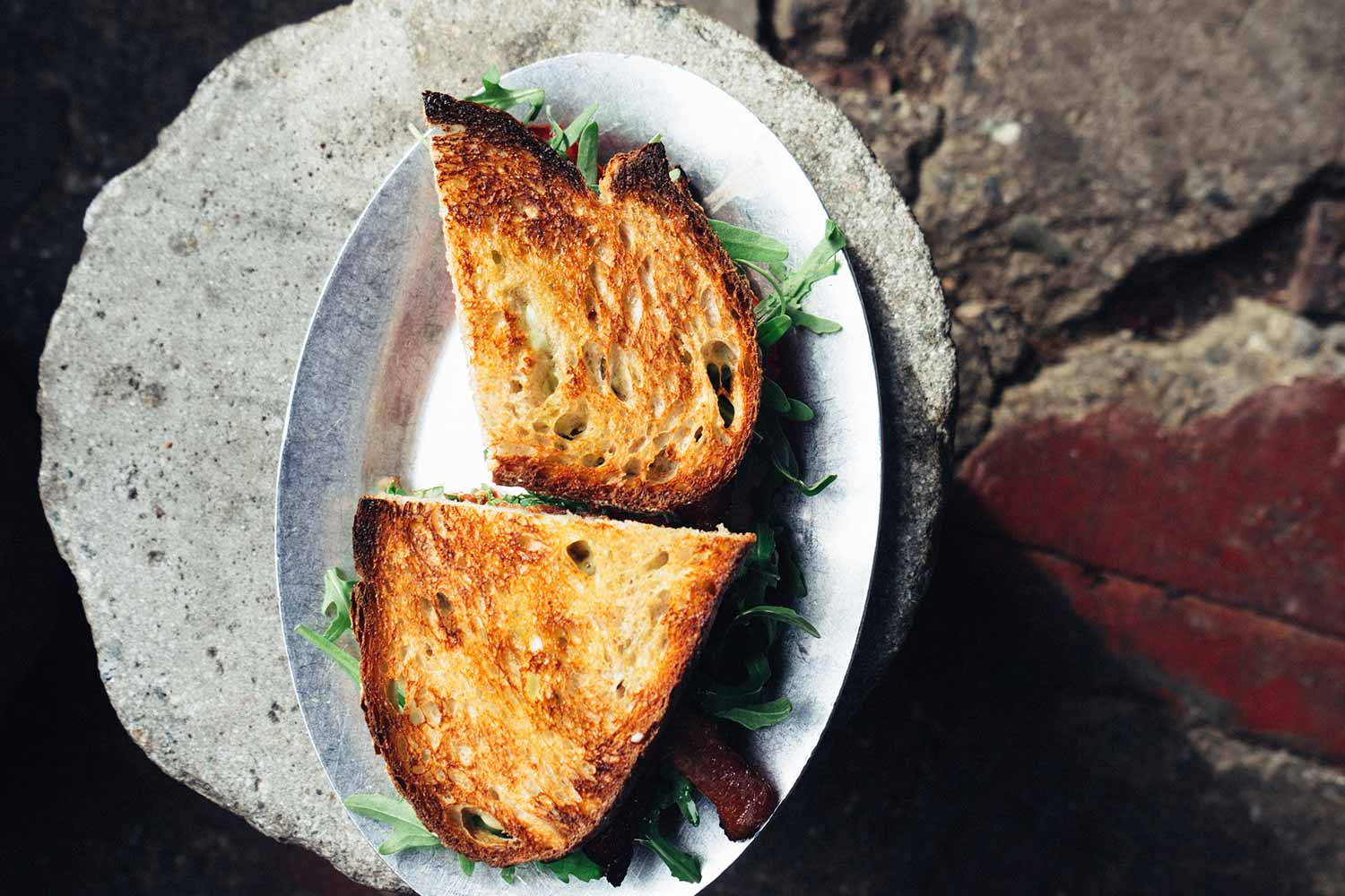 a toasted sandwich on a decorative plate
