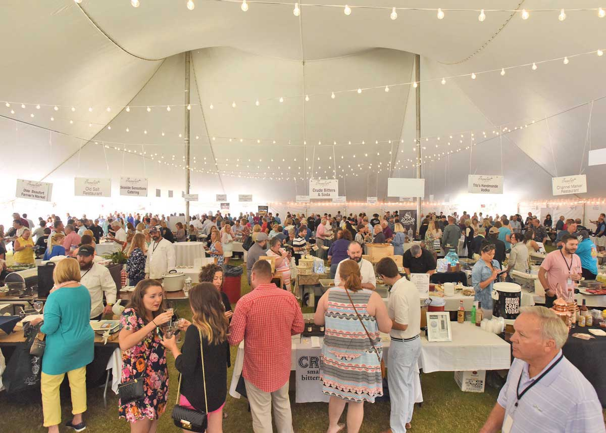 wine and food festival of large crowd under a white outdoor tent sitting at many different tables in a row